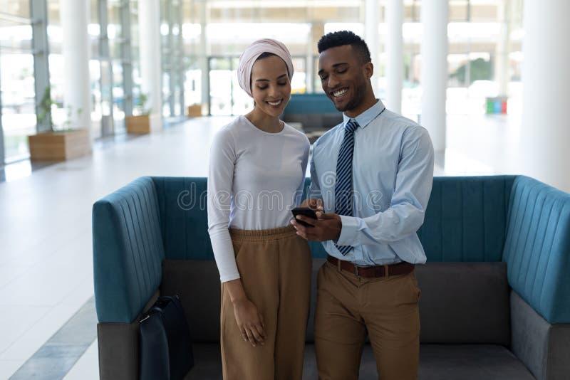 Młoda rasy para używa telefon komórkowego w lobby fotografia royalty free