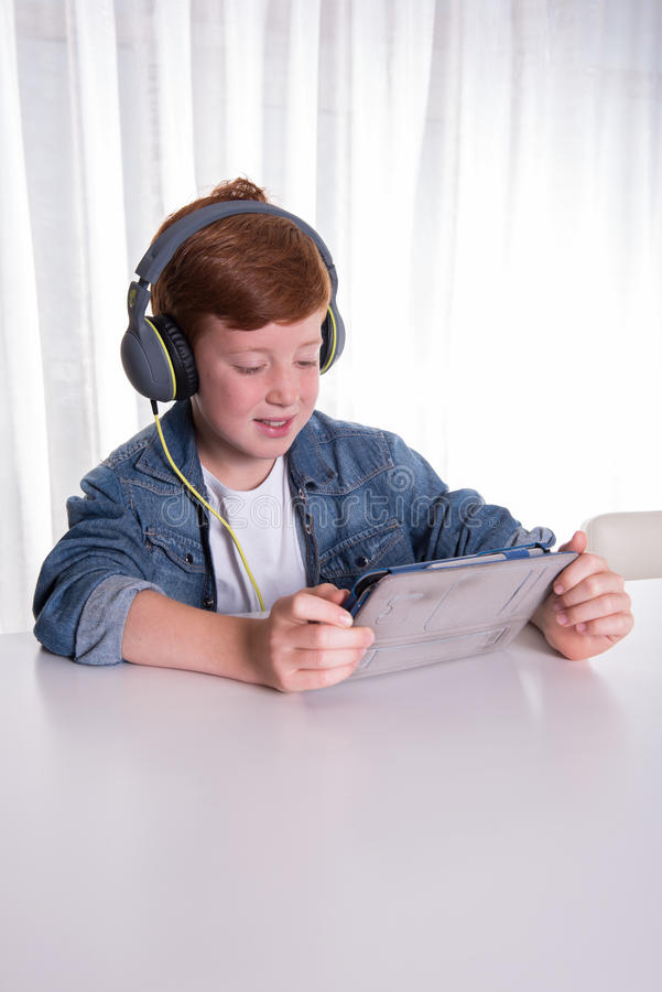 Młoda redhaired chłopiec patrzeje film na pastylce zdjęcia royalty free