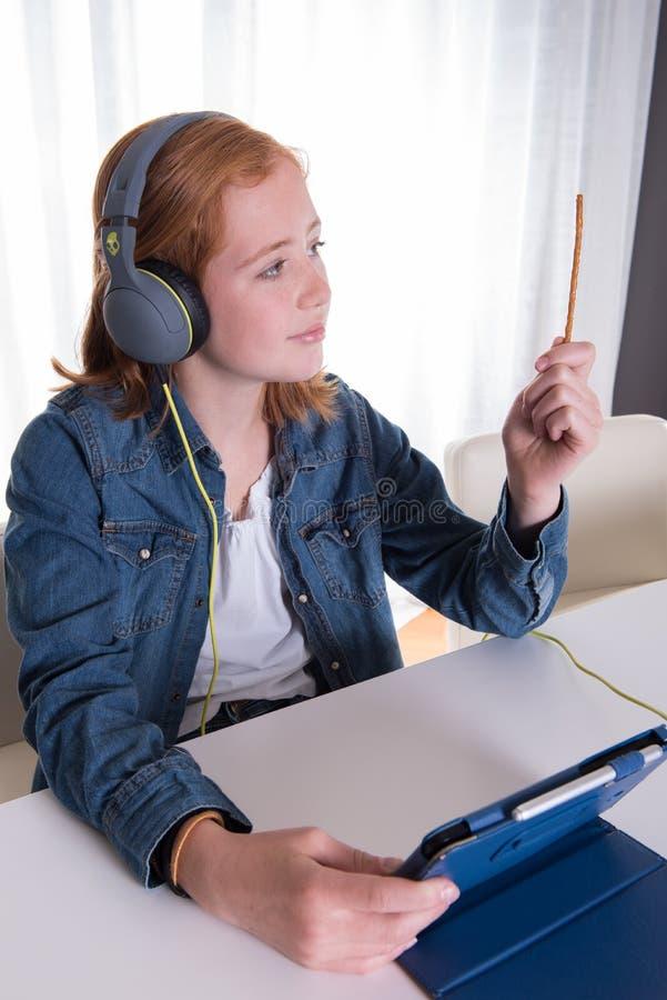 Młoda redhaired dziewczyna patrzeje film na pastylce zdjęcie stock