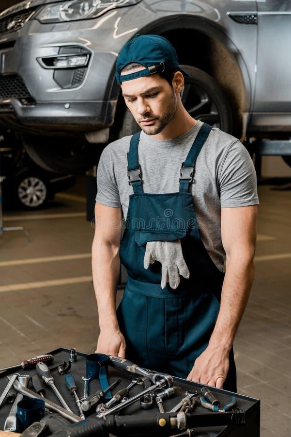 młoda repairman pozycja przy tabletop z mechaników narzędziami obraz stock