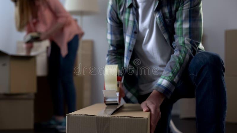 Młoda rodzina pakuje ich rzeczy w pudełkach, rusza się od dormitorium swój dom obrazy royalty free