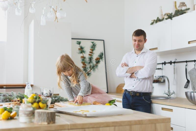 Młoda rodzina robi ciastkom w domu Robić piernikowemu ciastku z dzieciakami przy boże narodzenie czasem obraz stock