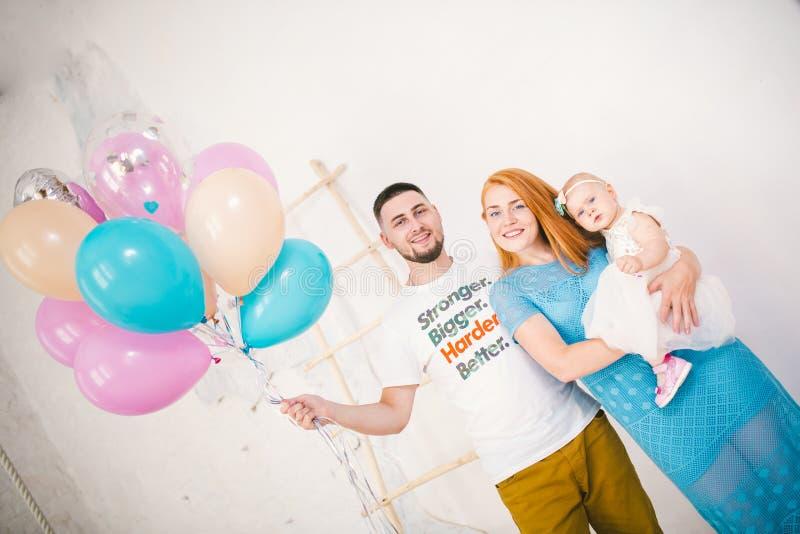 Młoda rodzina trzy ludzie, mamy ` s tata i córki ` s jeden roczniaka stojaki wśrodku pokoju, Trzymać balon w jej ręce, w obraz stock