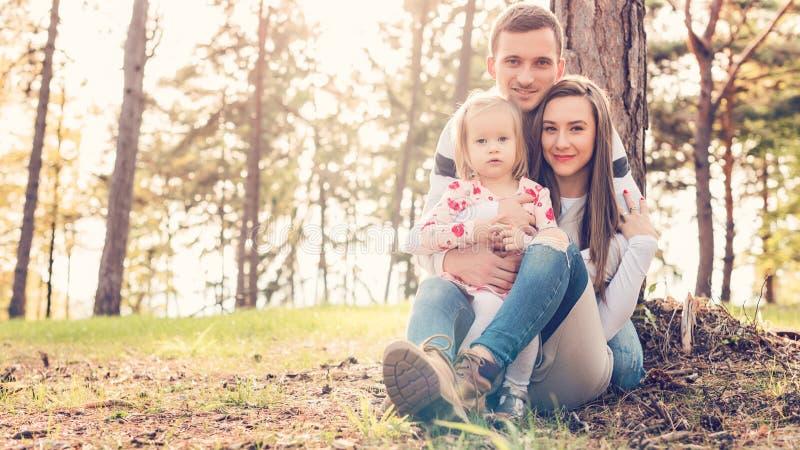 Młoda rodzina trzy ma zabawę w parku cieszy się ich czas wpólnie Istni ludzie, autentyczności pojęcie zdjęcie royalty free