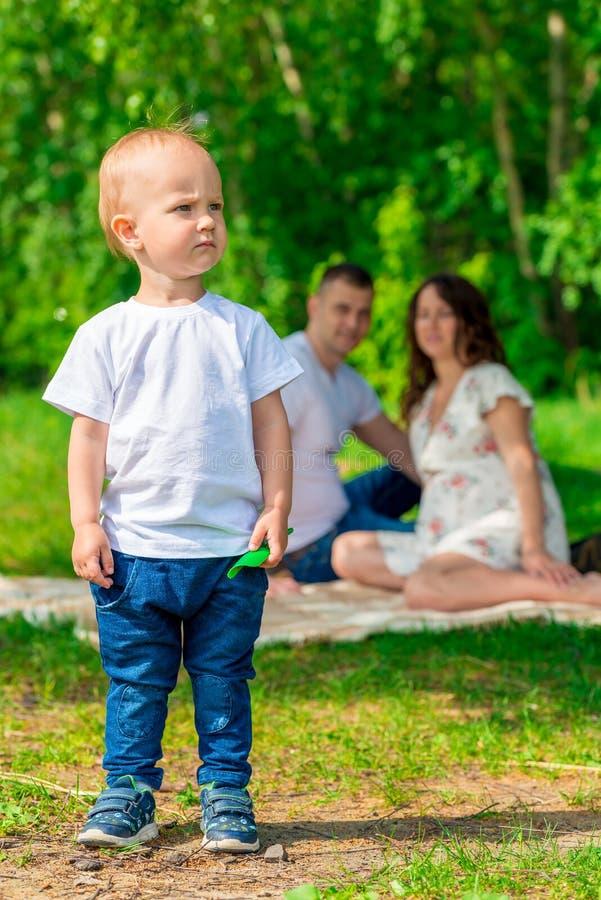Młoda rodzina w parku przy pinkinem w górę portreta, obraz royalty free
