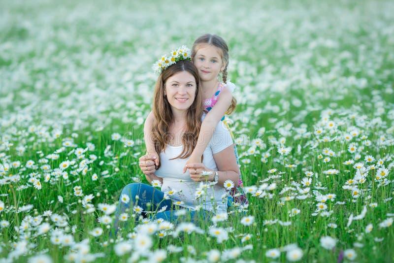 Młoda rodzina w polu kwiatów podiów chamomile zdroju anjoy życie szczęśliwy wraz z ślicznymi twarzami w wioska wieśniaka ruchu zdjęcie stock