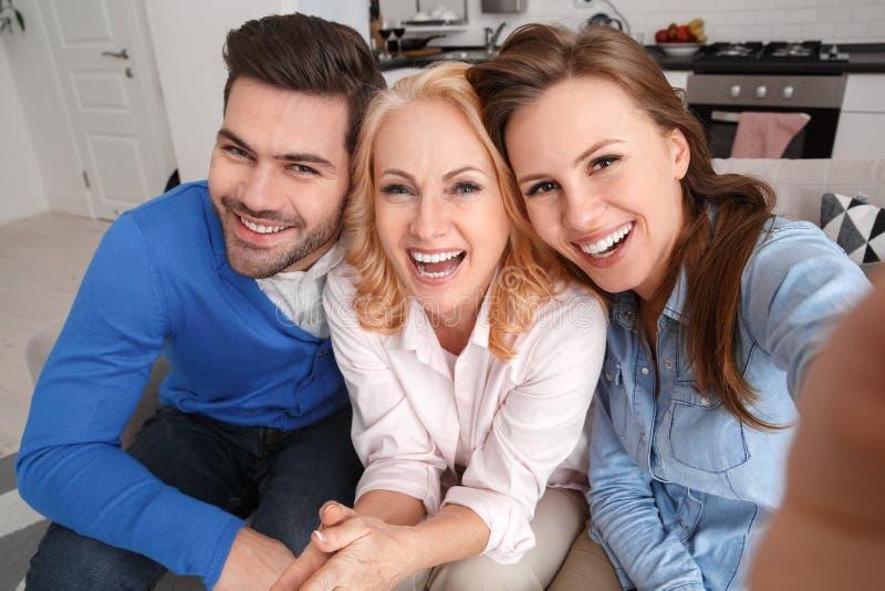 Młoda rodzina z świekra weekendem bierze selfie w domu obrazuje odgórnego widok zdjęcia stock
