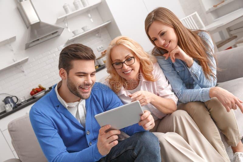 Młoda rodzina z świekra weekendem w domu używać cyfrową pastylkę zdjęcia stock