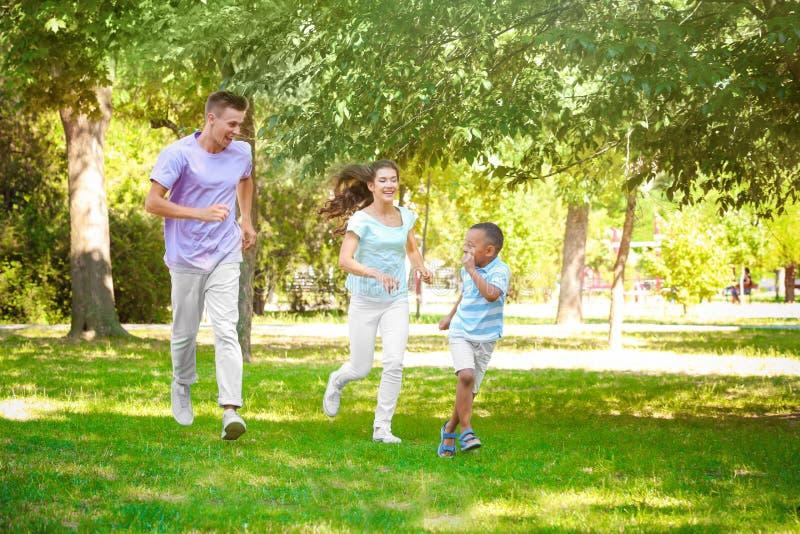 Młoda rodzina z adoptowaną amerykanin afrykańskiego pochodzenia chłopiec zdjęcia stock