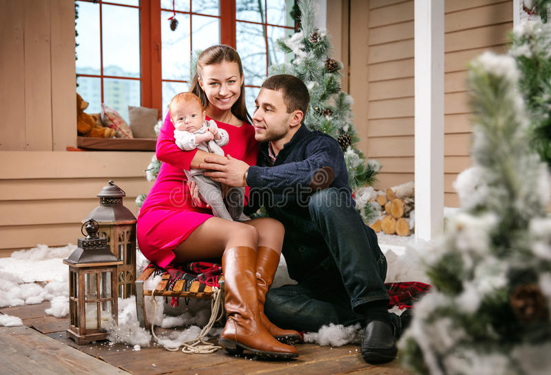 Młoda rodzina z chłopiec obsiadaniem na saniu w Bożenarodzeniowych dekoracjach zdjęcie stock