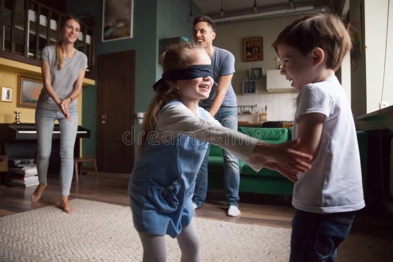 Młoda rodzina z dwa dziećmi bawić się aport zdjęcia royalty free