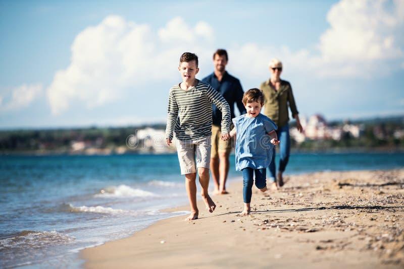 Młoda rodzina z dwa małymi dziećmi chodzi outdoors na plaży obrazy stock