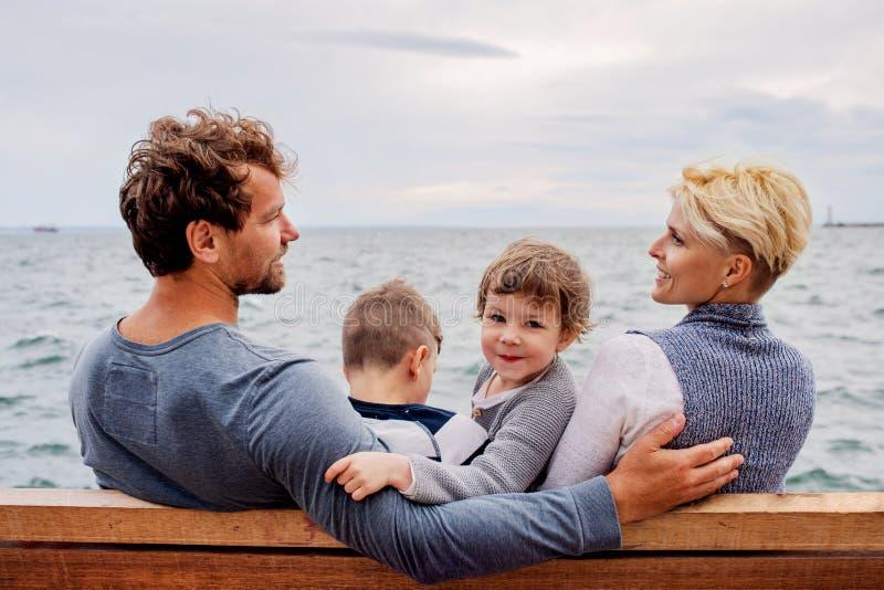 Młoda rodzina z dwa małymi dziećmi siedzi na ławce outdoors na plaży obrazy stock