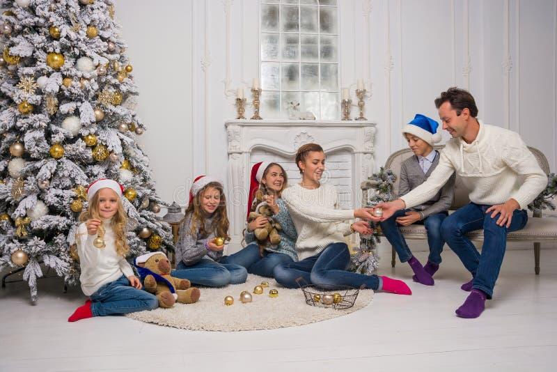 Młoda rodzina z dziećmi przygotowywa świętować boże narodzenia zdjęcie royalty free