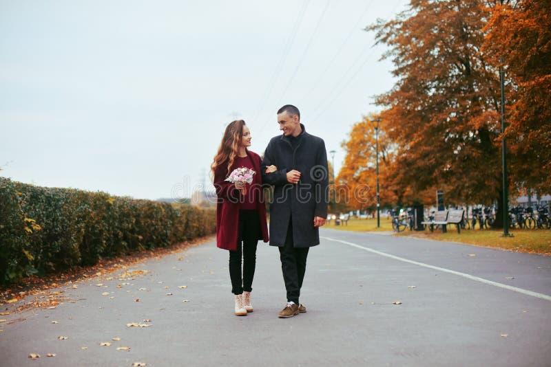 Młoda romantyczna para, piękna dziewczyna z kwiatami datowanie w parku Mężczyzna w szarym płaszczu i modelu w czerwonym żakiecie  fotografia royalty free