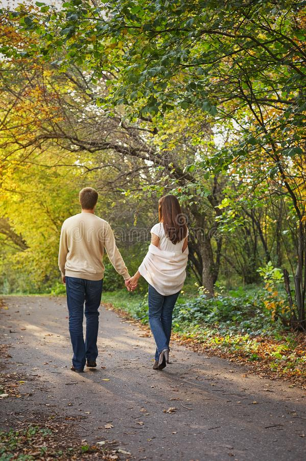 Młoda romantyczna para w miłości chodzi w jesień parka mienia rękach zdjęcie royalty free