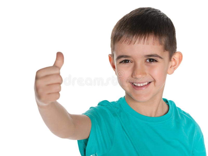 Młoda roześmiana chłopiec trzyma jego kciuk up zdjęcia stock