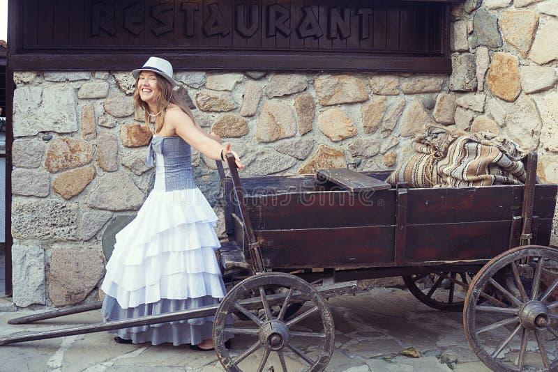 Młoda roześmiana kobieta pozuje w starym miasteczku blisko tradycyjnej restauracji zdjęcie royalty free