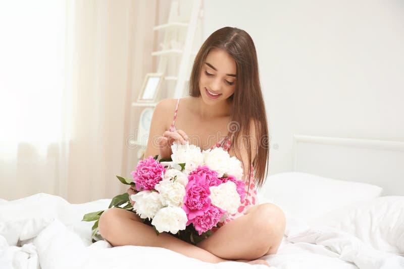 Młoda rozochocona kobieta z pięknym bukietem peonie siedzi w łóżku obraz stock