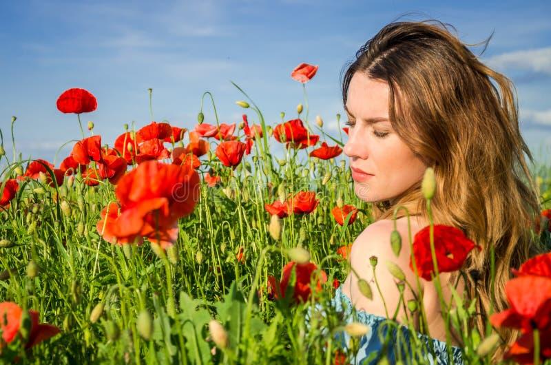 Młoda rozochocona piękna dziewczyna chodzi w makowej łące wśród czerwonych kwitnących maczków na jaskrawym, gorącym, pogodnym let fotografia royalty free