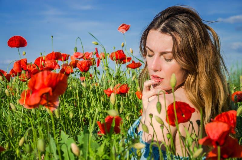 Młoda rozochocona piękna dziewczyna chodzi w makowej łące wśród czerwonych kwitnących maczków na jaskrawym, gorącym, pogodnym let obraz royalty free