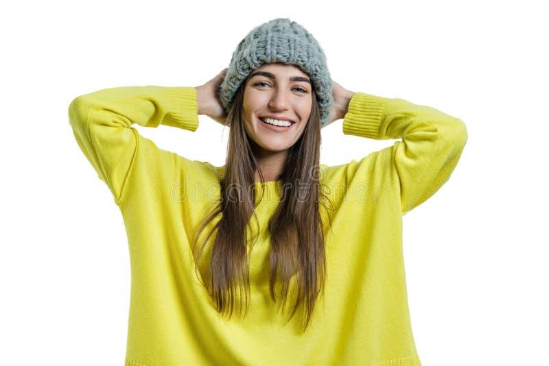 Młoda rozochocona piękna kobieta w żółtym pulowerze i szarej dużej pętli dział beanie kapeluszowego patrzejący kamerę na bielu od obrazy stock