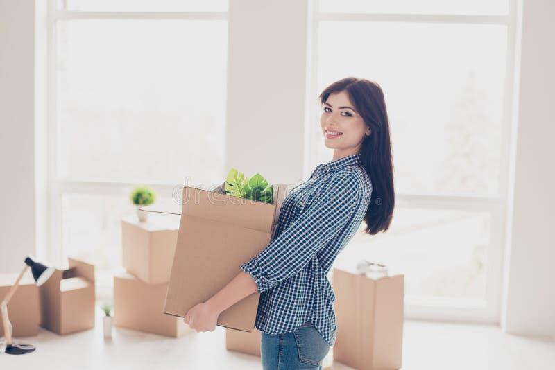 Młoda rozochocona pomyślna kobieta rusza się nowy ładny miejsce i hol zdjęcia stock
