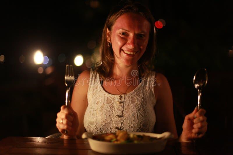 Młoda rozochocona uśmiechnięta kobiety mienia łyżka i rozwidlenie w plenerowej kawiarni przy morzem na pięknych bokeh światłach fotografia stock