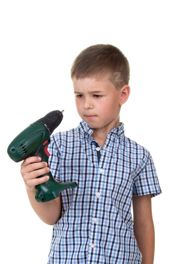 Młoda rozważna budowniczy chłopiec w szkockiej kraty koszula trzyma śrubokręt, odizolowywającego na białym tle zdjęcie stock