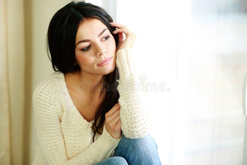 Młoda rozważna kobieta patrzeje okno obraz stock
