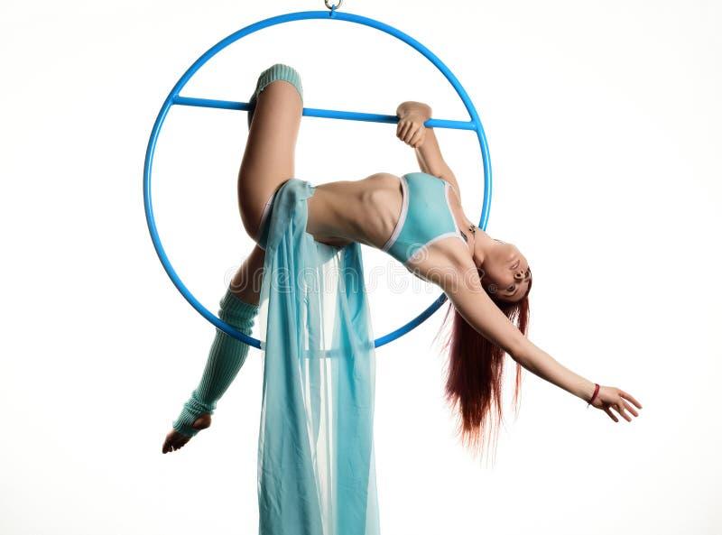 Młoda rudzielec kobieta wykonuje akrobatycznych elementy w wietrzy pierścionek na białym tle zdjęcia royalty free
