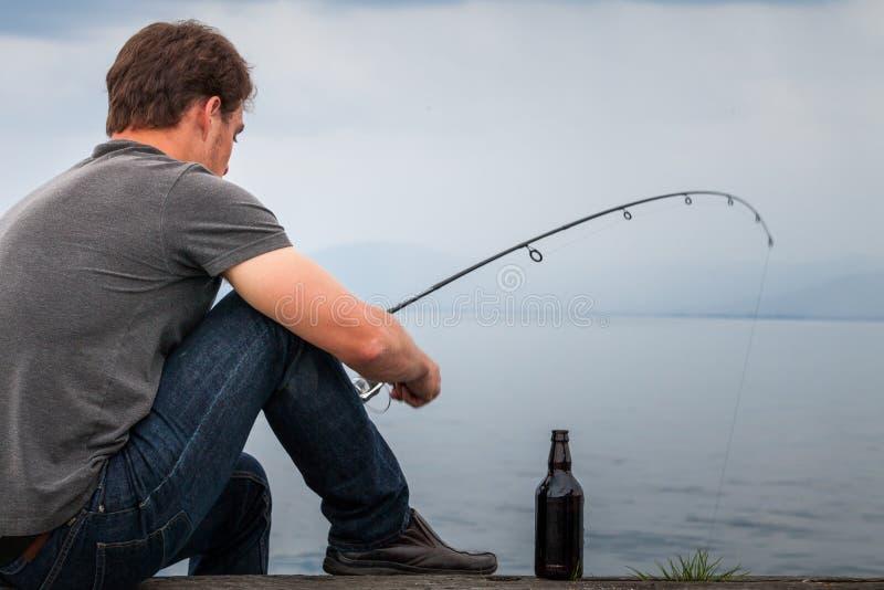 Młoda rybaka połowu makrela siedział na doku obrazy stock