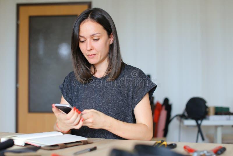 Młoda rzemieślniczka bierze obrazki handmade notatnik używać smartphone obrazy stock