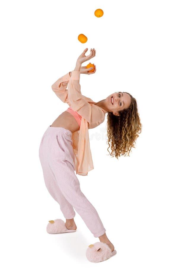 Młoda słodka kobieta w piżamie i kapcie żongluje tangerynami zdjęcia stock