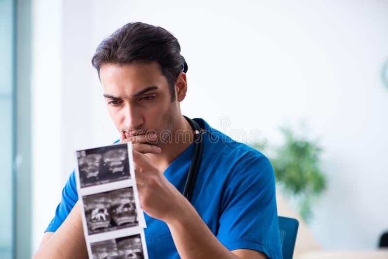 Młoda samiec lekarka patrzeje Doppler wizerunki obrazy stock
