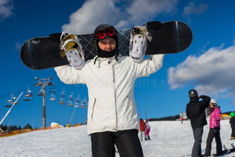 Młoda samiec w kostium pozyci i mienie jego snowboard na jego zdjęcia stock