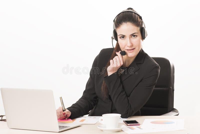 Młoda sekretarka odpowiada wezwanie z słuchawki fotografia stock