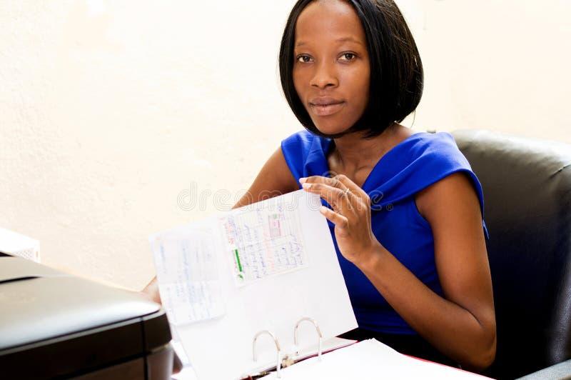 Młoda sekretarka przy jej biurem przy pracą fotografia stock