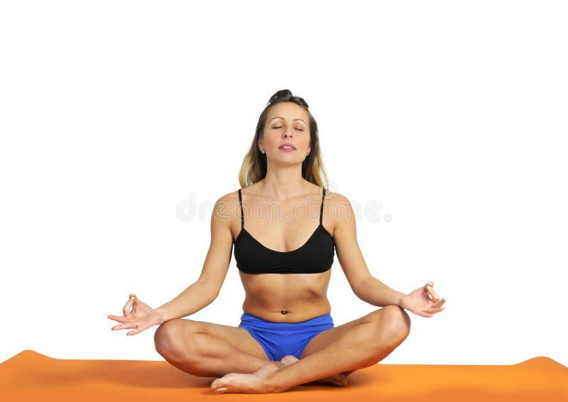 Młoda seksowna atrakcyjna dysponowana kobieta przy gym robi joga ćwiczeniu i pozyci obsiadanie na macie w medytaci i relaksujemy obraz stock
