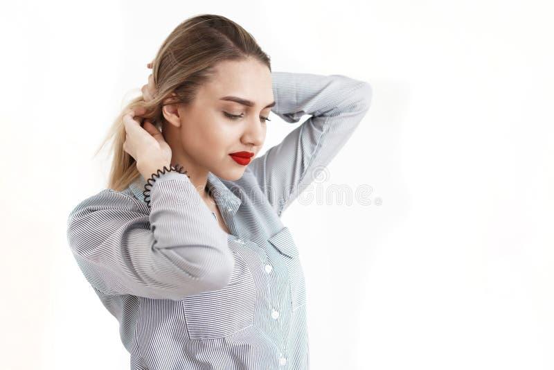 Młoda seksowna blondynka z jaskrawymi wargami prostuje włosy, biały tło zdjęcie stock
