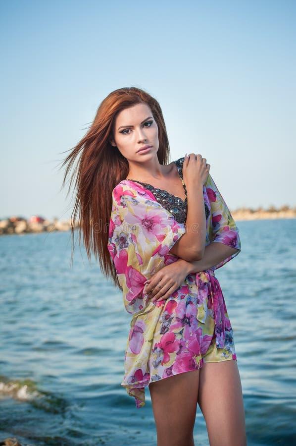 Młoda seksowna czerwona włosiana dziewczyna w stubarwnej bluzce pozuje na plaży Zmysłowa atrakcyjna kobieta z długie włosy, lato  obraz stock