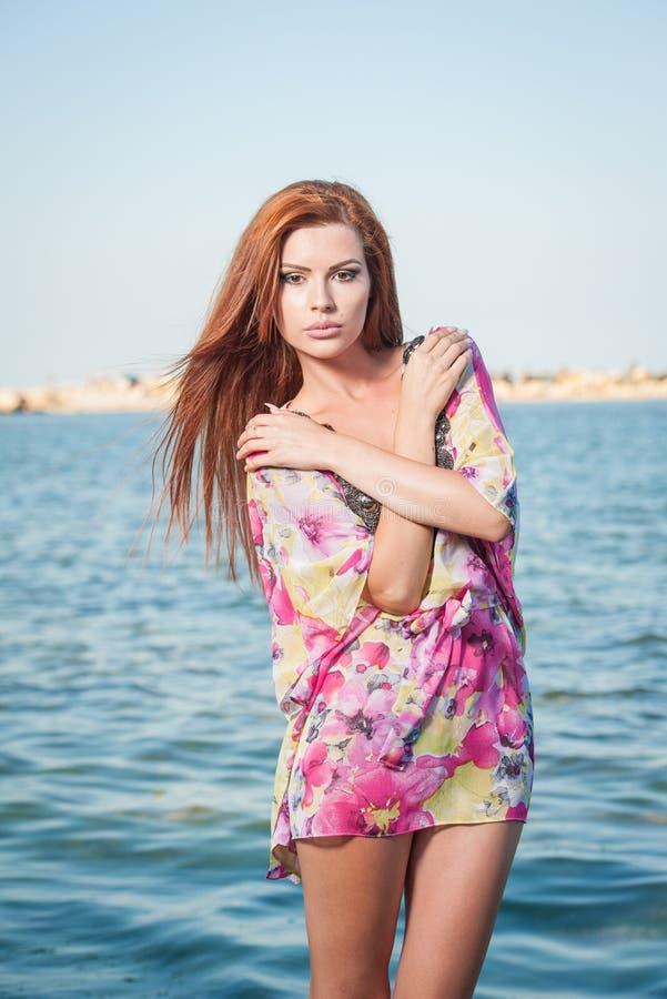 Młoda seksowna czerwona włosiana dziewczyna w stubarwnej bluzce pozuje na plaży Zmysłowa atrakcyjna kobieta z długie włosy, lato  zdjęcia stock