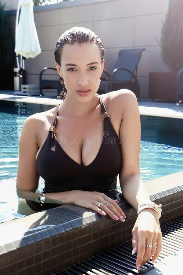 Młoda seksowna dziewczyna siedzi w pływackim basenie z dużymi piersiami fotografia royalty free