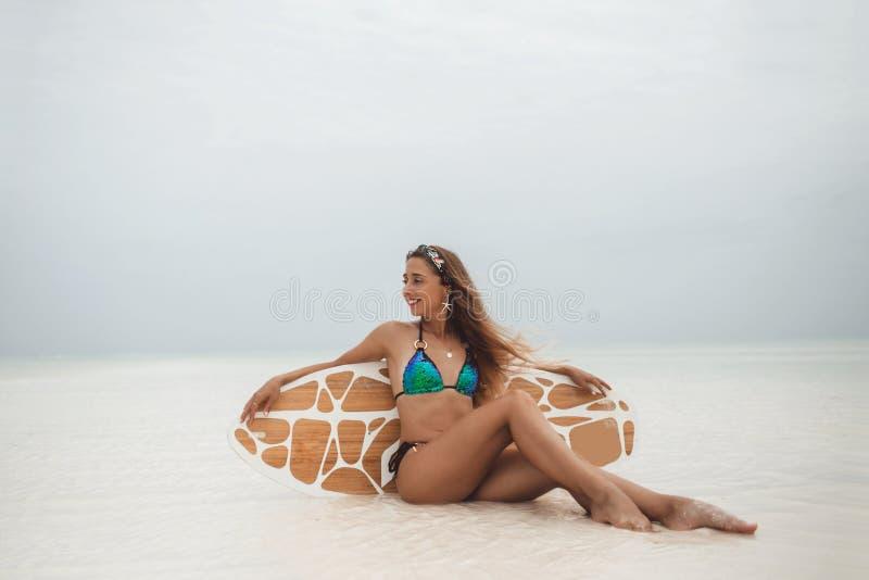Młoda seksowna kobieta z sportive garbnikującym ciałem siedzi na kipieli desce na plaży w letnim dniu cloudly podczas niskiego pr obraz royalty free