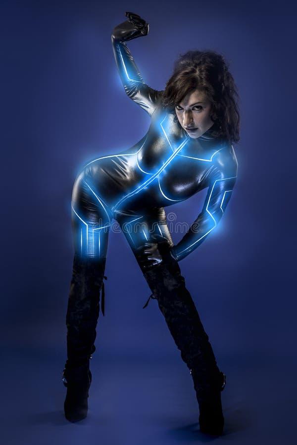 Młoda seksowna lateksowa kobieta na przyszłościowym kostiumu, błękitni neonowi światła obraz royalty free