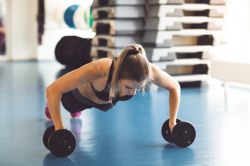 Młoda silna dziewczyna robi Ups na dumbbells w gym zdjęcia royalty free