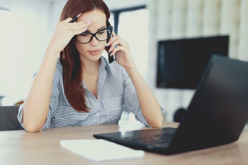 Młoda skrzętna energic freelancer kobieta dzwoni przy laptopem zdjęcie stock