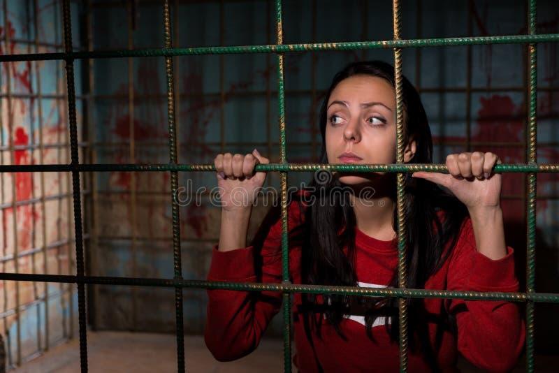 Młoda smutna żeńska ofiara więziąca w metal klatce z krwią obraz royalty free
