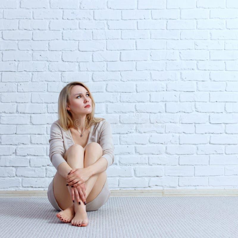 Młoda smutna kobieta w smokingowym obsiadaniu na podłoga i patrzeć daleko od obraz stock