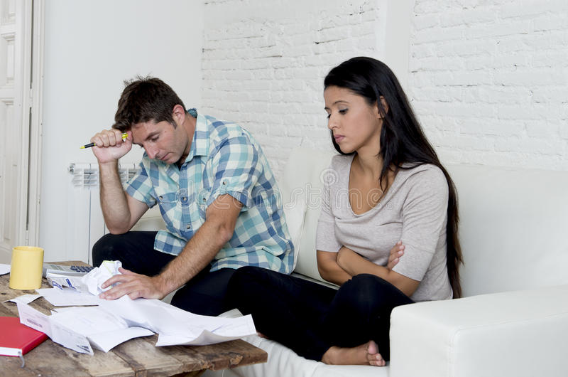 Młoda smutna para żyje izbowej leżanki kalkulatorskich miesięcznych koszty w domu martwił się w stresie obrazy stock